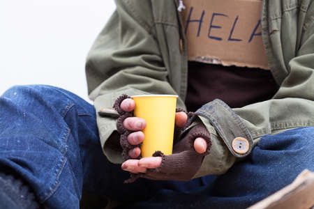 begging: Hands of homeless person holding a yellow, paper cup Stock Photo