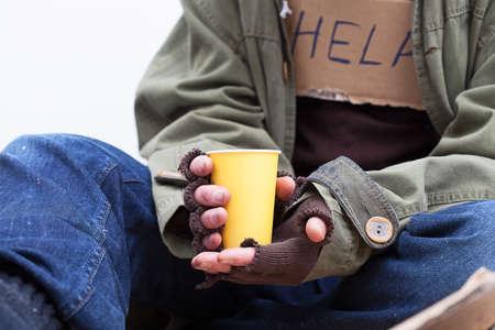 Ręce bezdomny trzyma papierowy kubek żółty,