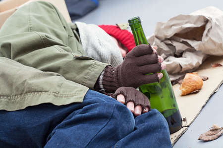 pauper: Homeless alcoholic with bottle of wine on a street