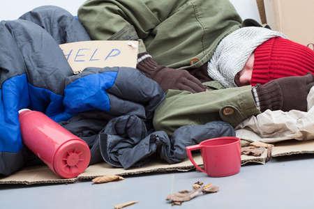 Dakloze man slapen op karton met slaapzak en thermoskan Stockfoto