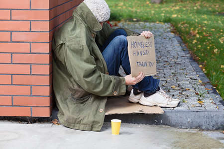 Poor homeless begging for money on a street photo