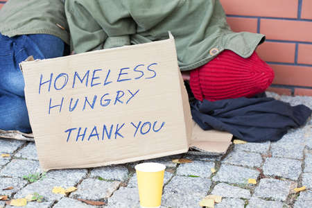 Homeless hungry poor man sleeping on a street photo