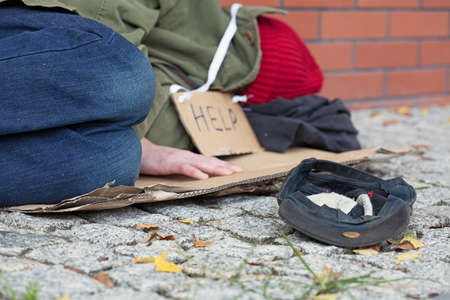Beggar falling asleep on the street with a cap for collecting money Stock Photo - 23049412