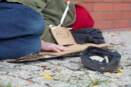 limosna: Mendigo quedarse dormido en la calle con una gorra de recogida de dinero