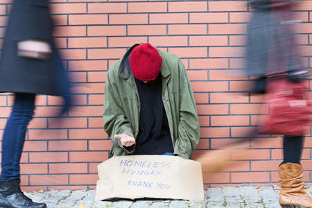 Homeless man sitting on a street passed by people Stock Photo - 23049413