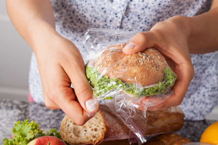 Mother foiling a sandwich for her child for a school meal photo