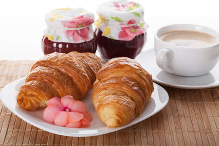 Coffe with fresh croissants and jar of jam photo