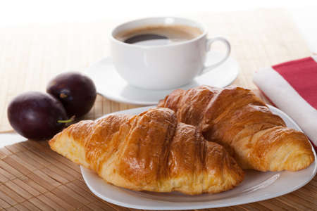 Two fresh croissants and cup of hot coffee photo