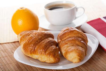 Coffee break with croissant and fresh juicy orange photo