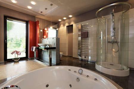 Роскошная ванная комната с ванной и стеклянной душевой Фото со стока