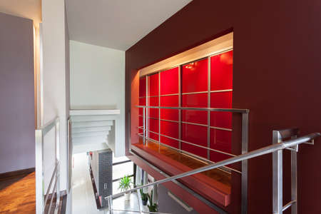 Red lighted wall and staircase in modern house Stock Photo - 23033915
