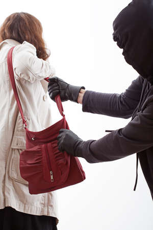 stealing money: Handbag thief is attacking a helpless woman and stealing bag