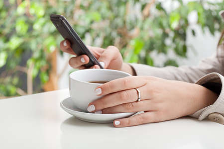Woman is sitting in cafe, drinking coffee and phone calling photo