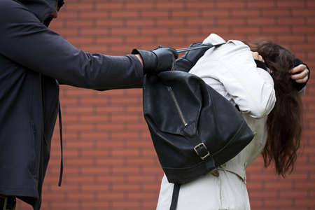 Dangerous masked man is assaulting a student to steal a backpack Stock Photo - 23256176