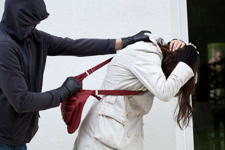 holdup: Hooligan is assaulting a woman to attempt to steal her bag