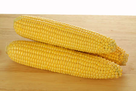 dietetical: Three yellow conr cobs on the plank