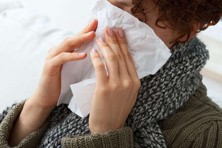Sick woman is blowing her nose to wipe photo