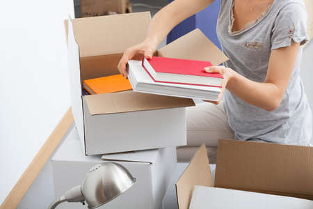 living things: Woman is packing her books and stuff to move flat Stock Photo