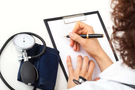 Doctor making medical notes in medical office Stock Photo - 23256496