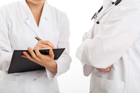 Doctors discussing and taking notes, isolated background Stock Photo - 23256503
