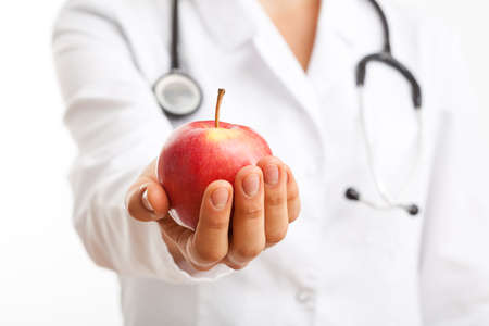 recommending: Doctor holding apple and recommending healthy lifestyle