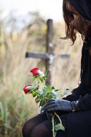 mujer llorando: Viuda a las rosas rojas holdig cementerio en sus manos Foto de archivo