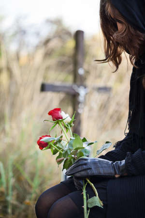 grieve: Widow at the cemetary holdig red roses in her hands Stock Photo