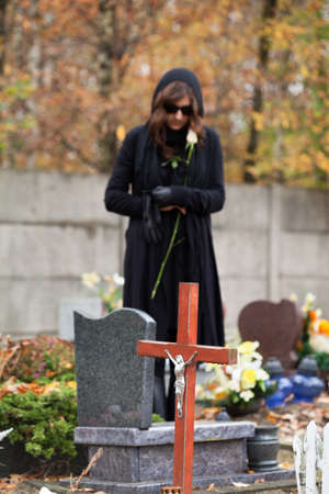 Woman in black standing above headstone holding white rose Stock Photo - 23256526