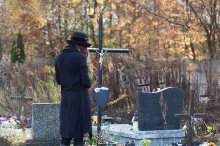 Woman in mourning clothes standing above headstone Stock Photo - 23256528