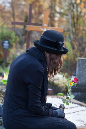 Woman dressed in black sitting at cemetery and holding red rose Stock Photo - 23256529