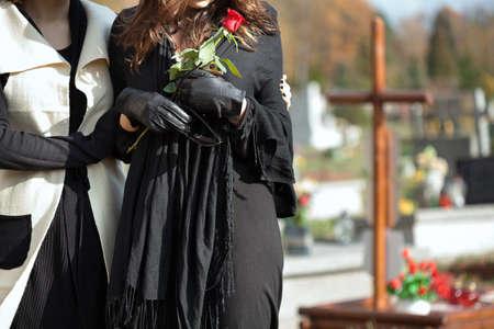 家族の墓の上に立っている彼女の娘を持つお母さん