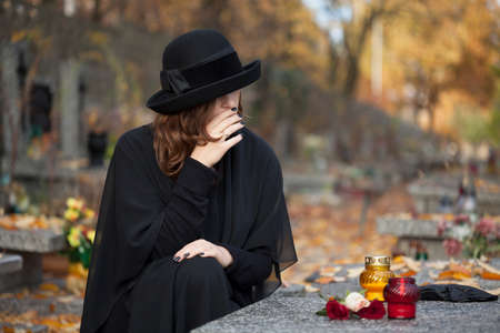 Woman in deep sorrow dressed in black at graveyard Stock Photo - 23256535