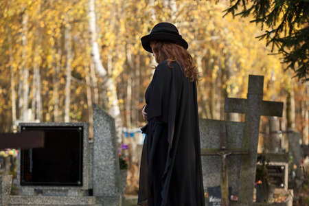 Lonely widow dressed in black standing over her husband's gravestone Stock Photo - 23256539
