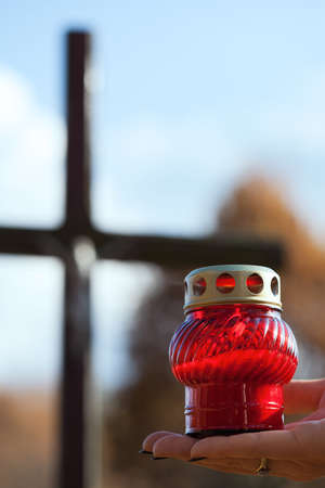 Red candle held on hand with a cross in the background Stock Photo - 23256542