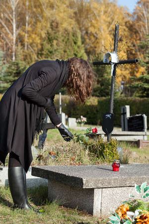 Widow in black putting red rose on grave Stock Photo - 23256543