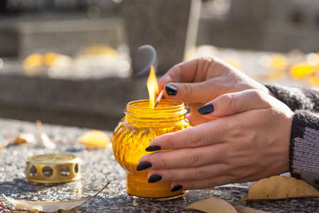 Woman at cemetery is lighting a yellow candle