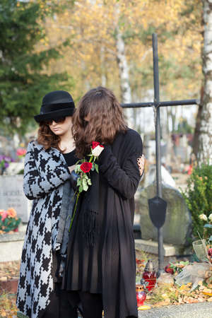 Two women standing above gravestone on autumn day photo