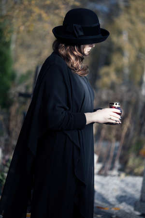 widow: Young woman dressed in black at cemetery holding a candle