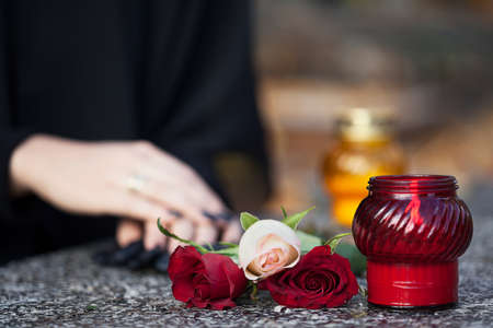 Woman in mourning arranging flowers and candles on the gravestone Imagens