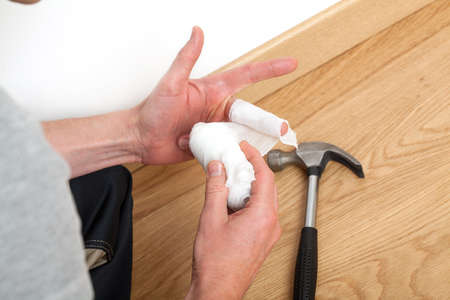 work accident: Accident at work- a man bandaging injured finger