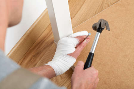 Man with injured finger repairing broken table with a hammer photo
