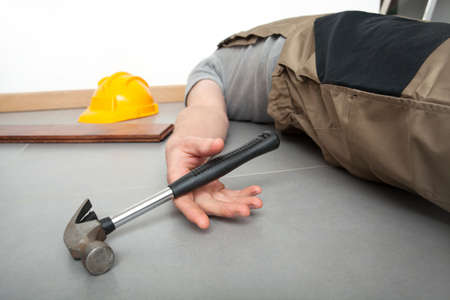 Unconscious worker lying on the floor with hammer in the hand Stock Photo