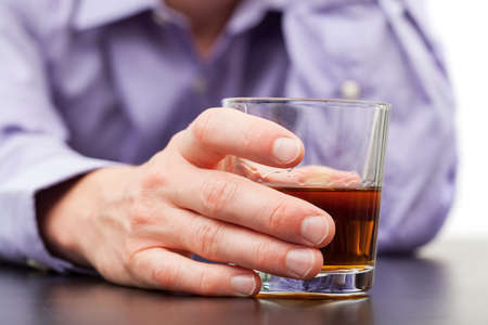 drinking problem: Businessman holding in hand glass of whisky