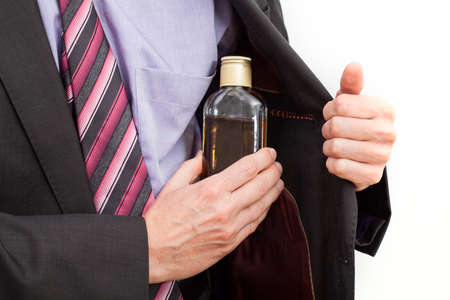 alcoholism: Businessman hiding an alcohol bottle into his jacket Stock Photo