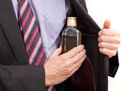 alcoholismo: Hombre de negocios que oculta una botella de alcohol en su chaqueta
