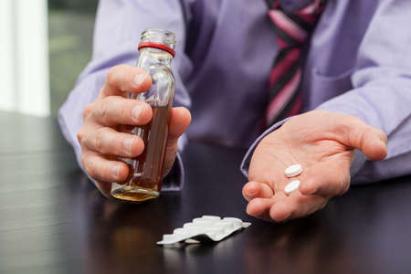 Man in suit with drugs and alcohol in hands photo