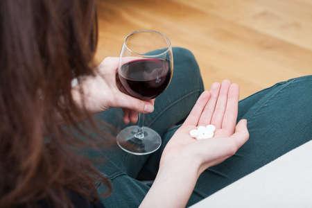 sobredosis: Mujer Addicted tomar drogas con alcohol Foto de archivo