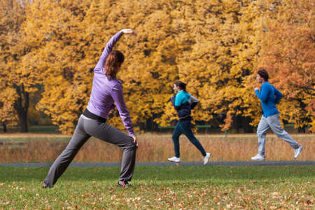 Young people exercising in park in autumn
