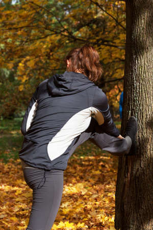 Autumn outdoor stretching in park, young woman photo