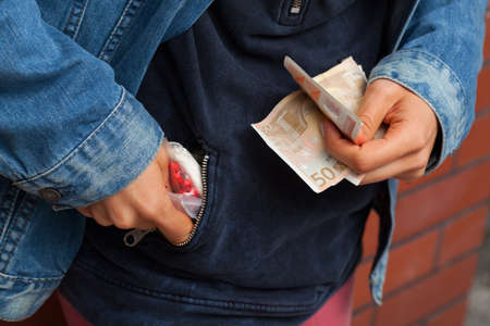 drug deals: Drug dealer hiding pills in his pocket and holding money in his hand Stock Photo